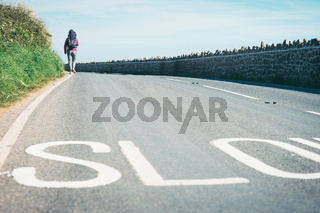 Female tourist, hichhiker, backpacker walking on the road to a distance in Rhossili, Wales