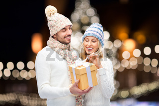 happy couple with christmas gift over night lights