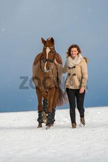 Frau mit Pferd im Schnee