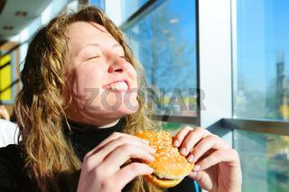 very happy woman is eating cheeseburger