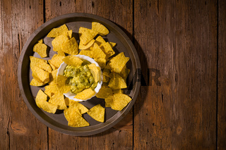 Nachos chips with salsa guacamole on a platter over an old wooden table
