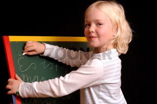 Mädchen schreibt auf einer Tafel