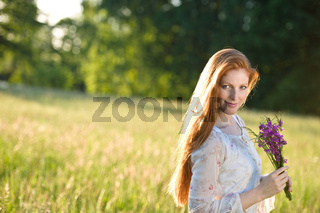 Long red hair woman in romantic sunset meadow