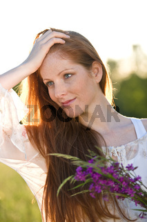 Long red hair woman with bouquet of flower