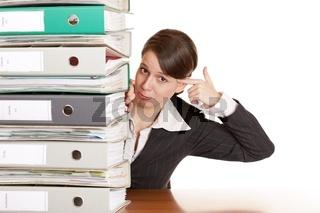 Frustrierte Frau hinter Aktenordnern gibt sich Kopfschuss