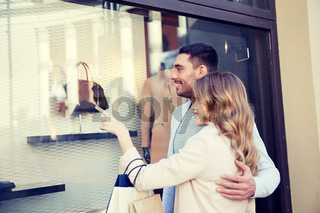 happy couple with shopping bags at shop window