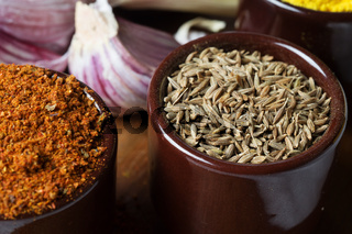 Spices and herbs in ceramic bowls. zira seasoning. Colorful natural additives.