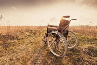 Empty wheelchair on the meadow at sunset - vintage retro version