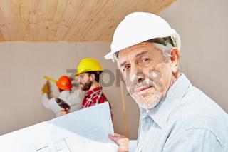 Senior als Vorarbeiter mit Bauplan
