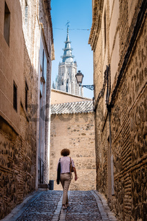 Woman walking by narrow street with tower of Toledo Cathedral
