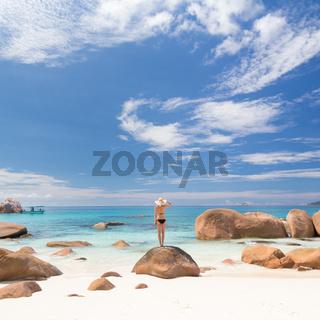 Woman enjoying Anse Lazio picture perfect beach on Praslin Island, Seychelles.