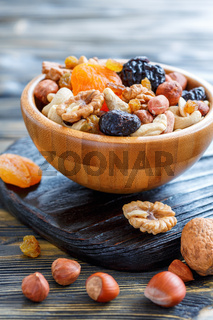 Dried fruit and mixed nuts in a wooden bowl.