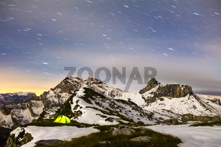Tent glows under a starry night sky in snowy alpine mountains. Alps, Switzerland.