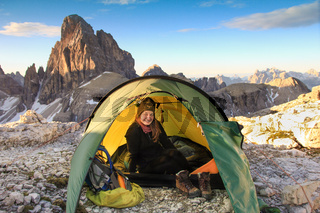 Woman sitting relaxed in tent and smiling happy. Great mountains.