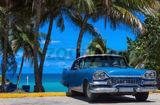 Amerikanischer blauer Oldtimer parkt am Strand unter Palmen in Varadero Kuba
