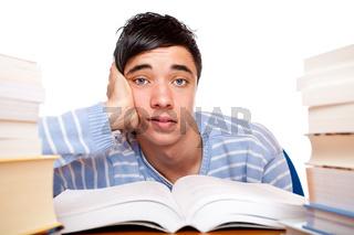 Hübscher männlicher Schüler sitzt frustriert zwischen Schulbüchern und lernt auf Prüfung