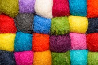 color wool background - balls of synthetic wool yarn - geometric rainbow pattern