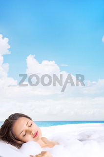 Young beautiful woman relaxing in bathtub in outdoor tropical spa resort