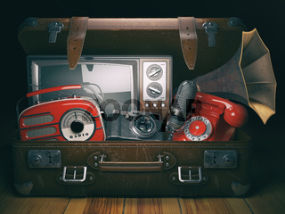 Vintage suitcase with old obsolete electronic equipment set. Retro technology concept background. Radio, tv set, telephone camera microphone and gramophone.
