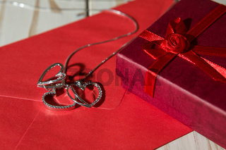Closeup of silver heart pendants on a red envelope and gift box