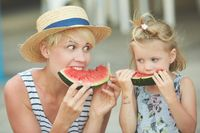 Mother And Daughter Enjoying Slices Of WaterMelon
