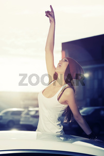 Happy fashion woman in tank top shouting beside a her car