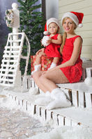 Mom and daughter in Santa's suits are sitting under snow