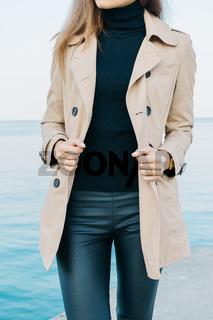Slim elegant girl in a beige coat and black pants on the sea background