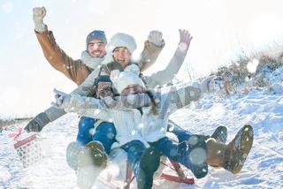 Familie beim Schlitten fahren im Winter