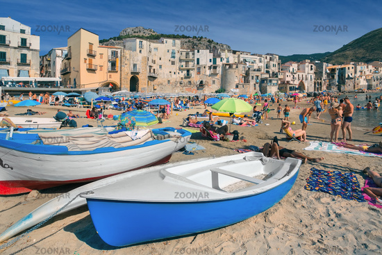 Unidentified people on sandy beach in Cefalu, Sicily, Italy