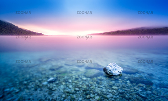 Long exposure of rock in lake at pebble beach with purple sunrise light.