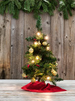 Small Christmas tree decoration on rustic wood with evergreen branches in background