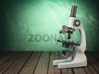 Microscope on wooden table and green vintage background