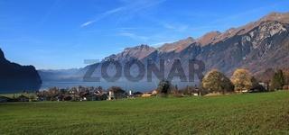 Autumn scene in Brienz. Green meadow, houses and lake Brienzersee. Mount Augstmatthorn. Landscape in Switzerland.