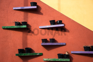 Blumentöpfe an einer farbigen Hauswand