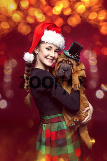 Pretty girl in christmas hat with shar pei puppy