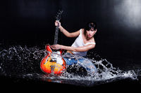 Rock-n-roll girl playing a guitar in water on black