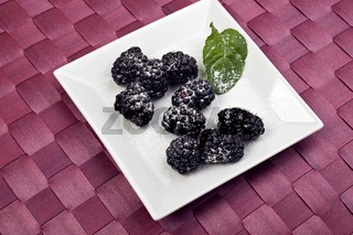 blackberries on a white plate with a peppermint leaf