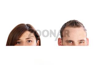 Junges Paar hinter einer Wand, nur die Augen sind zu sehen