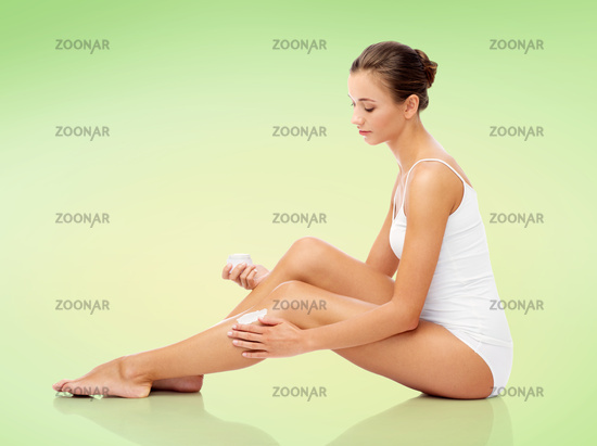 woman applying moisturizing cream to her leg