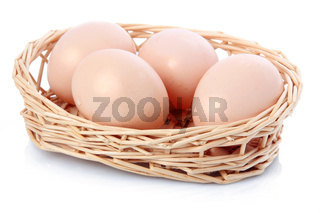 Raw eggs in basket isolated on white