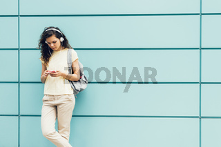 Girl in yellow t-shirt standing on a background of blue wall and listening to music on headphones with mobile phone