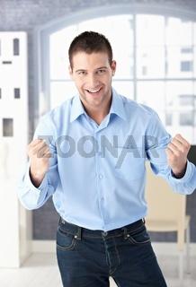 Happy man celebrating success smiling
