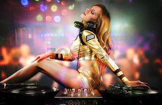 Beautiful DJ girl on decks playing on the party people on the dancefloor