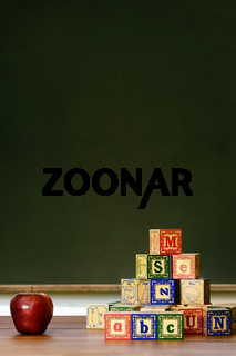 Apple and wooden blocks in front of blackboard