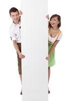 Junger Mann und Frau im Dirndl stehen lächelnd hinter Werbefläche. Freigestellt auf weissem Hintergrund.