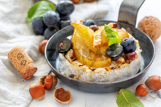 Grilled camembert with pears and black grapes.