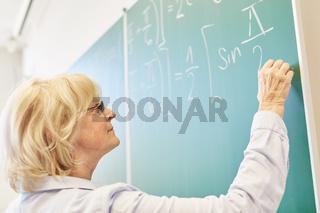 Ältere Mathe Dozentin an der Tafel
