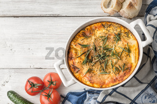 Moussaka in the white table with vegetable and bread top view
