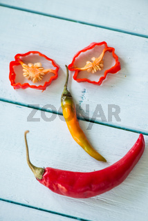 Smiling funny face made with hot chilli peppers on wood